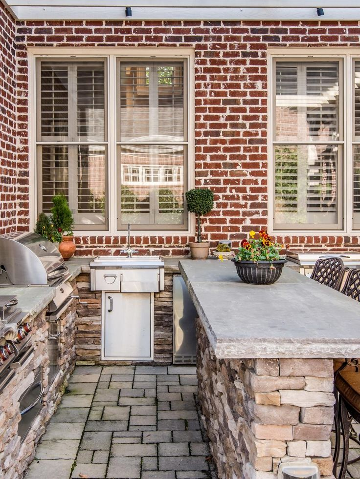 A stone bar with stools adjacent to the outdoor cooking area ensures that guests will be able to eat food fresh off the grill, and that the cook won't miss out on the party. A pergola offers shade during the day and overhead lighting at night.