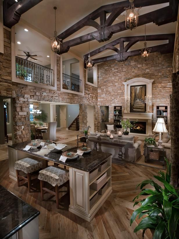 Two-Story Stone Great Room With Timber Trusses & Neutral Furnishings