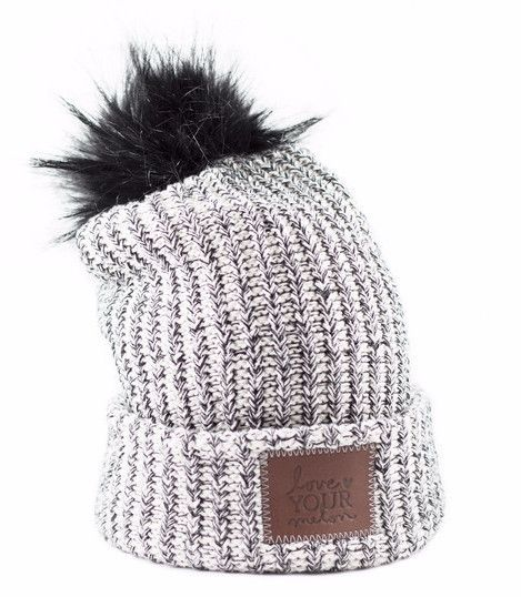 This pom beanie is knit out of 100% cotton yarn in natural and black colors. It features a brown leather patch that is debossed with the Love Your Melon logo and a detachable, black faux fur pom. Made