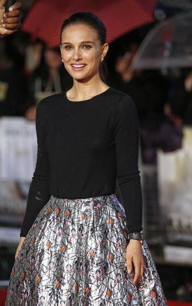 Natalie Portman, die het gezicht is van het parfum 'Miss Dior', kiest voor een outfit van de ontwerper: een sobere top en fleurige rok.