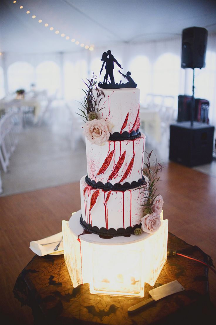 "Just look at this zombie wedding cake! We are so inspired by this Halloween Wedding at Heritage Prairie Farm. The cake was made by Black Forest Baking Company. We love the added roses and, of course, the ""blood"" dripping down from the brainssss! And the zombie cake topper is so perfect. Such a cool idea for a gothic wedding. Photo by Kris Kasperek Photography."
