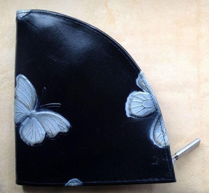 déqua - Geldbörse 'Segment' aus geprägtem Leder, schwarz, weiße Schmetterlingsmotive. Dieses Portemonnaie besticht durch seine ungewöhnliche Form und bietet sogar genügend Platz für das iPhone5 oder ein Handy mit ähnlichen Ausmaßen. Praktisch, extravagant, zum Verlieben!