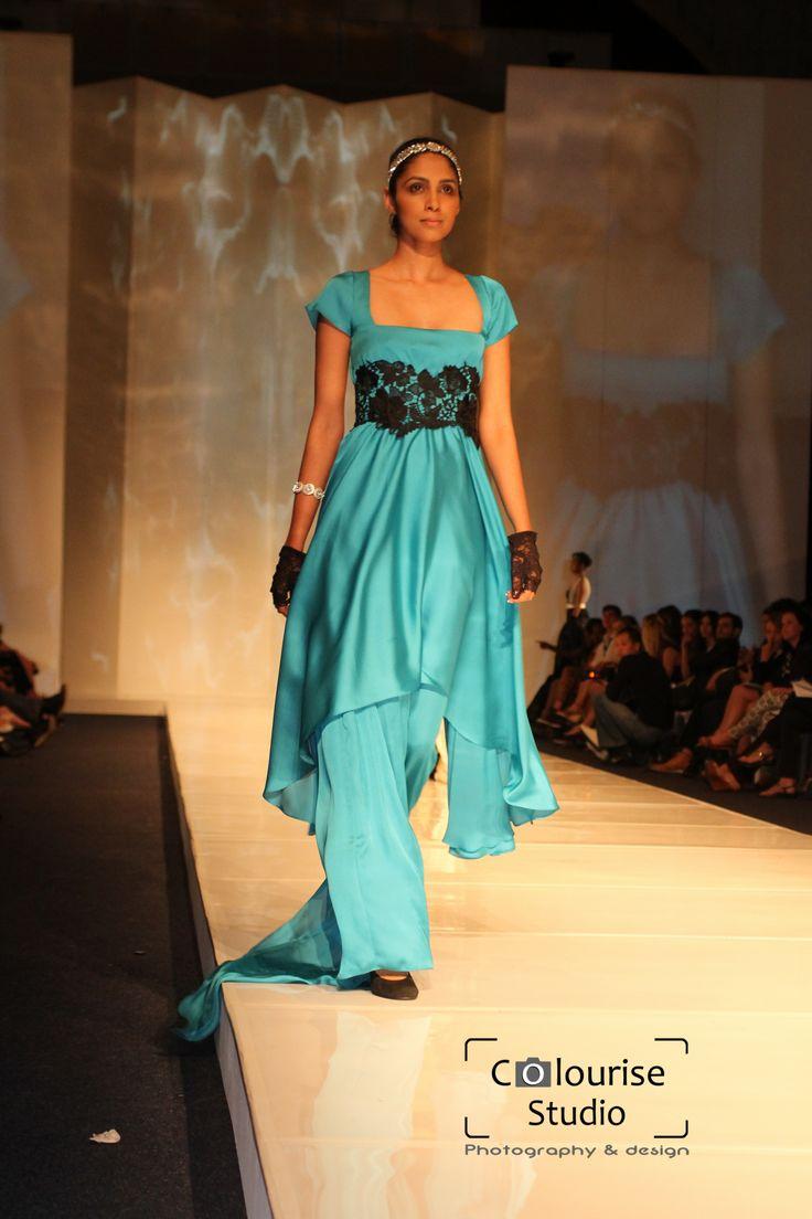 A gown of blue italian satin with an asymmetrical skirt overlay and hand sewn lace waistband.