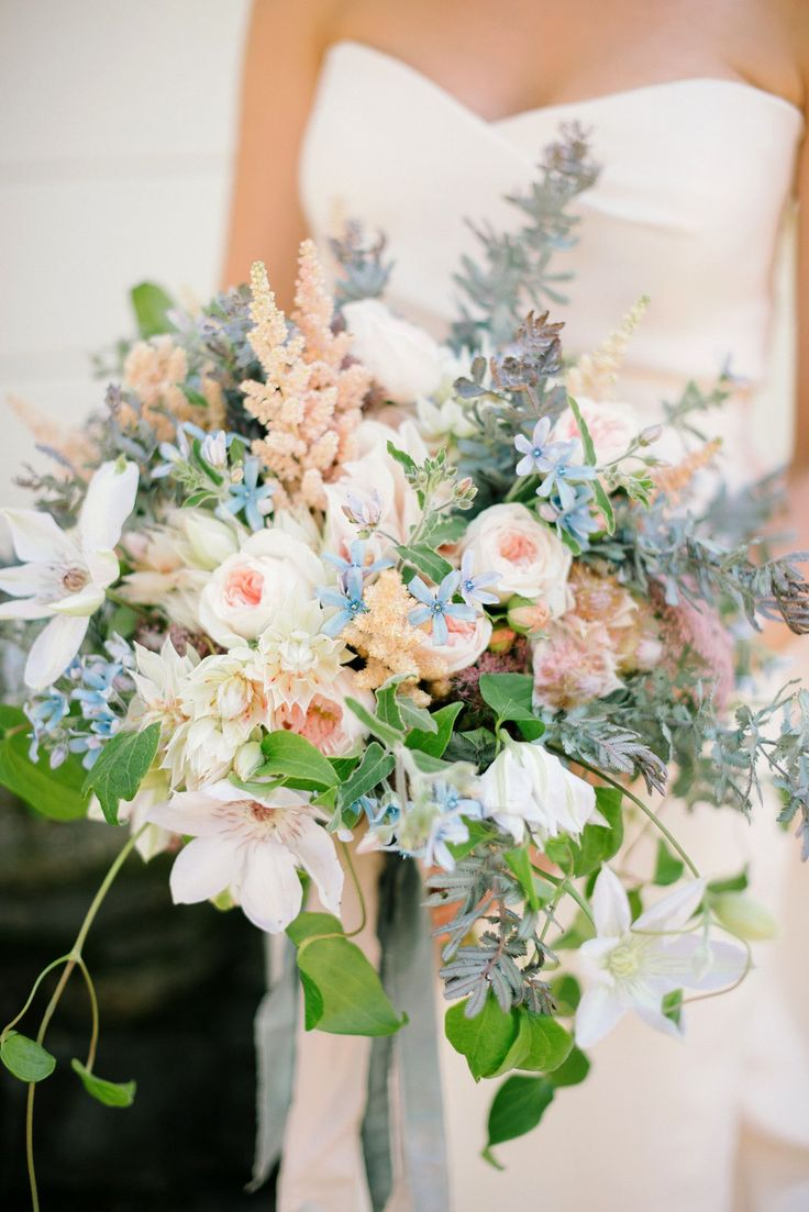 For Caitlin's garden-inspired wedding, only a bouquet brimming with flowers would do. That's where Chestnut and Vine came in, creating this lush arrangement of clematis, roses, astilbe, blushing bride protea, ranunculus, tweedia, Queen Anne's lace, and acacia foliage.