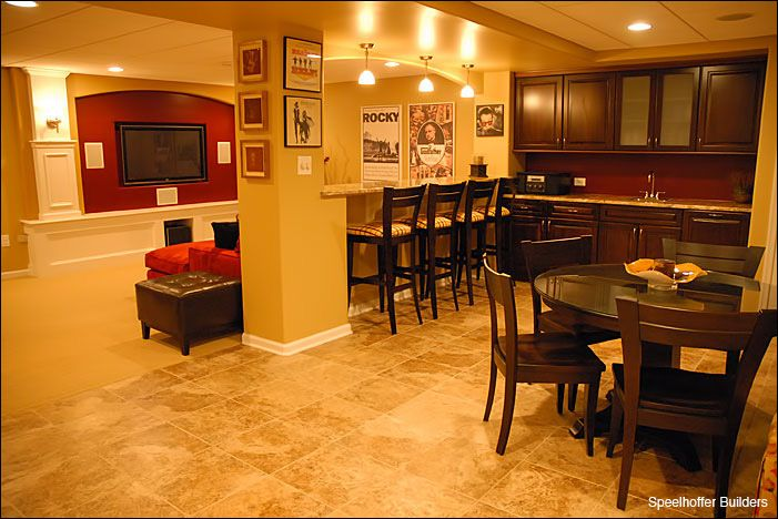 There is plenty to share with this renovated basement. The wall behind the TV stands out with a red backsplash, which matches the couch right in front of the HD TV. Guests and family can also view TV from the full wet bar. The extra family room in this basement also includes a dining table.