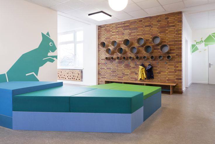 Sinnewandel Kindergarten in Berlin designed by Baukind and Atelier Perela. Paper tube shelving, coat hooks and irregular shaped colourful platforms - for playful flexible space.