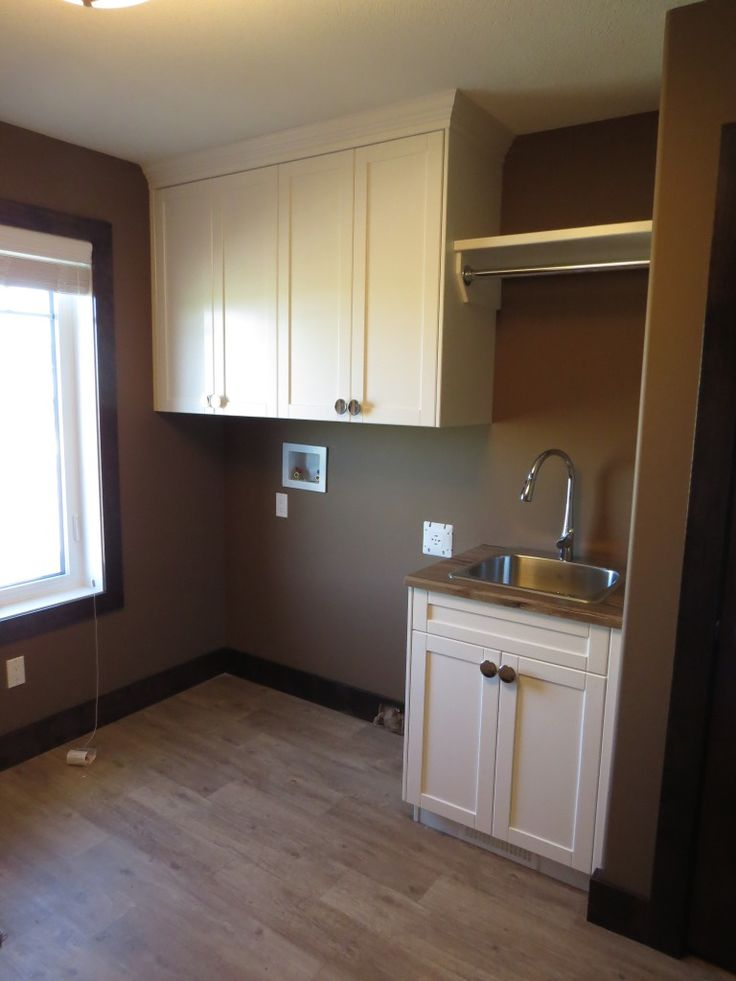 Custom Laundry Room with upper cabinets, and hanging rod as well as utility sink. #laundry