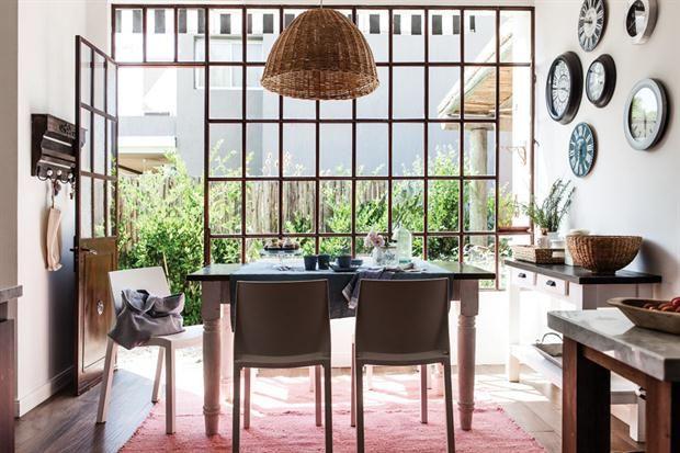 El comedor diario se ubicó frente al enorme ventanal de vidrio repartido que sale al patio posterior. La mesa antigua (Muebles de Antes) rodeada de sillas 'París' (Mascardi) está dispuesta sobre una alfombra en lana pura ($6.210, Elementos Argentinos). / Santiago Ciuffo