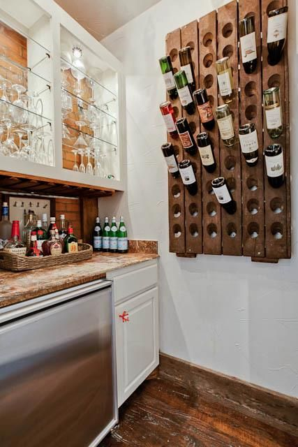 Fantastic butler's pantry features open upper cabinets accented and glass shelves over white lower cabinets with mini-fridge and wall-mounted riddling wine rack.