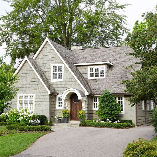 Adorable cottage with small details that make a big difference! Bright white trim adds contrast to the warm gray color scheme of this home. More entryway makeovers: http://www.bhg.com/home-improvement/exteriors/curb-appeal/entryway-designs/?socsrc=bhgpin060613wooddoor=4