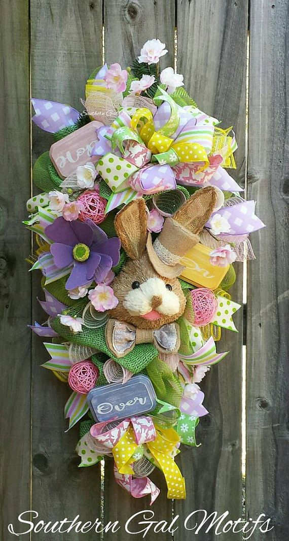 A beautiful Easter bunny swag for this upcoming Easter holiday! The swag measures a little over 24 in length. A wonderful Top hat Easter bunny centers the swag. Custom hand painted wood signs stating  HOP ON OVER accents the wreath design. A touch of whimsy is added with beautiful florals and spring ribbon bows. It is ready to ship today!  The swag will be shipped in a custom wreath box for easy storage later. Please hang swag under a protected area to prevent damage from the weather…