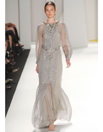Carolina Herrera Spring 2012  Evening was strictly glam with shades of Old Hollywood. Close your eyes and imagine Greta Garbo lounging in a sheer, long-sleeved gown speckled with silver embroidery.