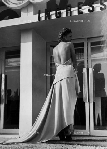 """Model seen from the back wearing an evening dress created by the couture house """"Graldi"""". The article is characterized by a bare back and train.1935 - 1939 (C) Bogino, LuisFratelli Alinari Museum Collections, Florence"""
