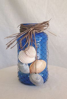 This is a recycled Ragu jar which has been painted inside then baked in the oven, it has a candle in side then is covered in netting with jute then sea shells from Tybee Island, Ga. This would be and attractive addition to any home.
