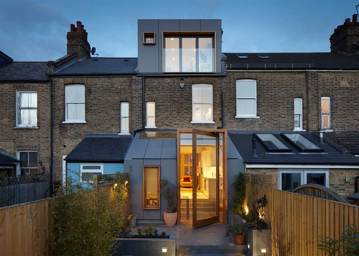 A three-metre-high pivoting glass door protrudes from the sloping roof of this extension to a Victorian terraced house in southeast London