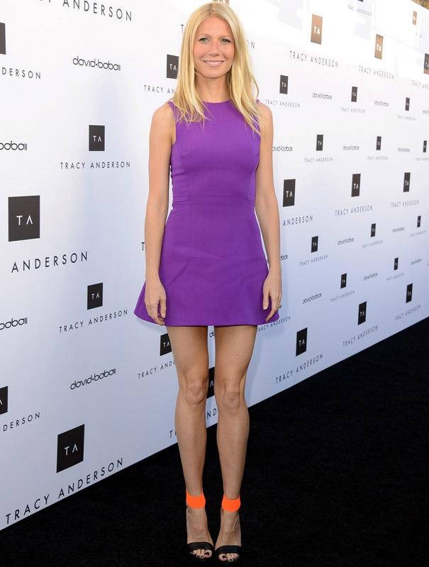 Gwyneth Paltrow  - Está claro que los tonos flúor van a ser la clave en zapatos para esta temporada. Nos encantan las sandalias en negro y naranja de Michael Kors que Gwyneth Paltrow luce con este minivestido morado de Victoria Beckham.