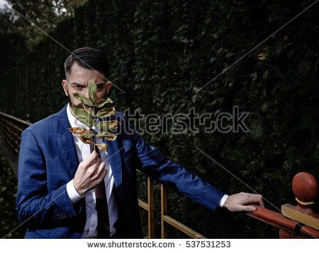 sexy man with piercing eyes in an elegant suit with a plant