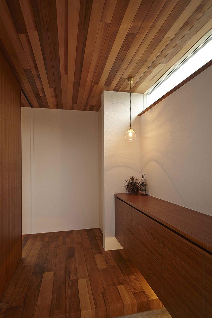 濃色の木と白壁のコントラスト。ハイサイドライトからの柔らかい光。靴箱の下の間接照明で浮遊感を強調。ペンダントライトも素敵。