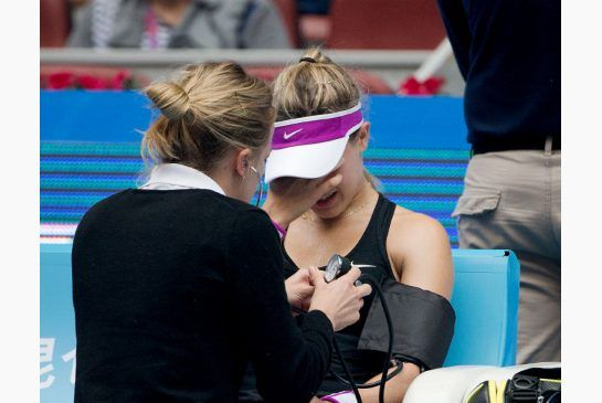 Eugenie Bouchard of Canada receives medical attention during her first round match against Andrea Petkovic of Germany in the China Open tennis tournament at the National Tennis Stadium in Beijing, Monday.
