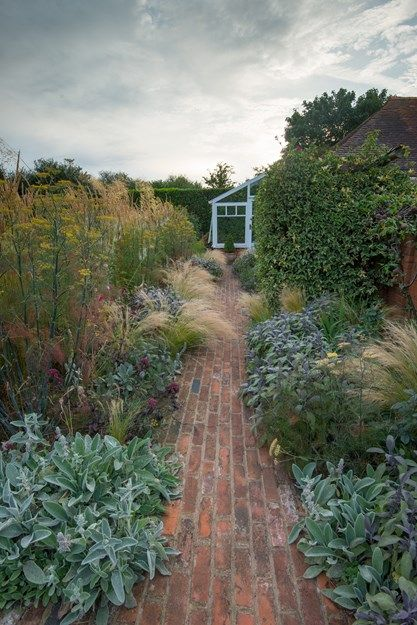 The gentle foliage of Mexican feather grass (Stipa tenuissima) spills onto a path of reclaimed red brick leading to the greenhouse. Lamb's ear (Stachys byzantine), purple sage, and bronze fennel make up the rest of the plant palette. Photo by: Elliot Hook.