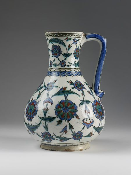 Jug Place of origin: Iznik, Turkey (made) Date: ca. 1575-1585 Jug of fritware, pear-shape, with a curved handle. Painted in red, blue, green and outlined in black under a clear glaze, with flowers and two reserve-painted fret bands round the mouth and the shoulder.