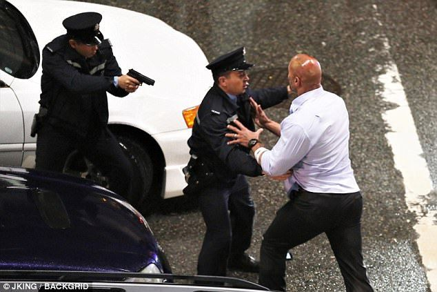 Drama: Dwayne Johnson was seen wrenching himself away from cops who tried to detain him as he shot scenes for his upcoming movie Skyscraper in Vancouver, Canada, on Thursday