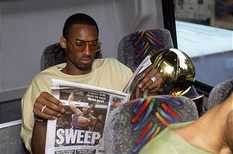 Guard Kobe Bryant #8 of the Los Angeles Lakers reads the headlines as he sits in the team bus with the championship trophy after winning Game Four of the 2002 NBA Finals against the New Jersey Nets at Continental Airlines Arena in East Rutherford, New Jersey on June 12, 2002. The Lakers defeated the Nets 113-107 and won the series 4-0.