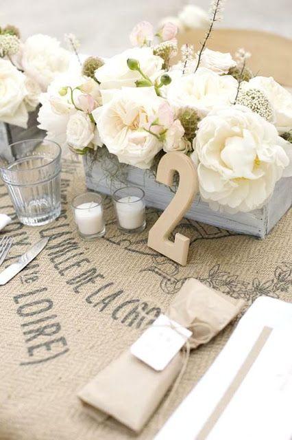 Sac en toile de jute en guise de nappe et petite caisse en bois pour accueillir des fleurs !