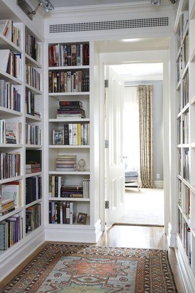 Floor to ceiling bookshelves in a hallway.