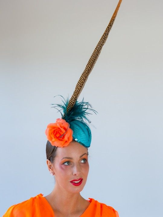 6FT HUSSY | Hat/Fascinator Melbourne Cup Carnival | FORD MILLINERY  $365  She's tall, she's elegant and BY GEORGE she's a hussy! 1950′s air-hostess style base made of aqua buntal straw, hand-trimmed with aqua sequins, fluorescent orange organza rose, deep aqua/teal feather tree and one gloriously long (70-80cm) golden pheasant tail feather. Golden metallic hair comb to secure (additional hat/hair pins are recommended as an additional item). Spruce up a monochrome number, or go bold with…