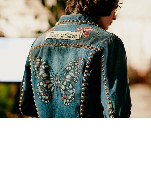 A look at the back of a men's denim jacket from #GucciPreFall16, featuring a mix of studs, hand-painted flowers and a butterfly. #AlessandroMichele