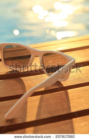 Sunglasses on wooden planks and water on sunset
