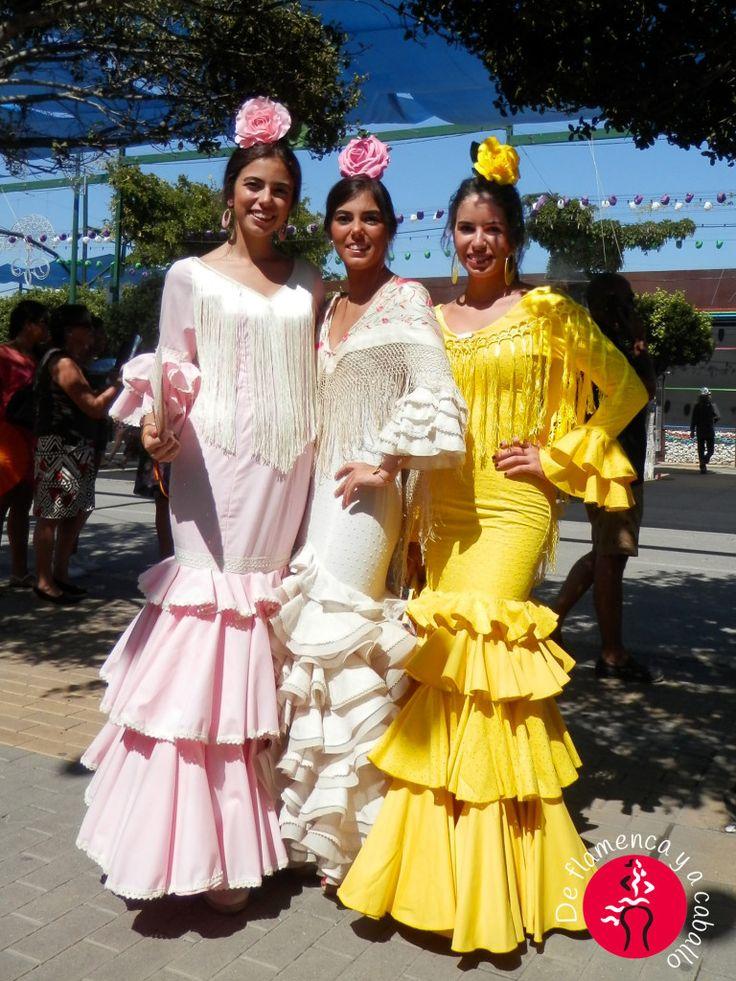 Grupo de mujeres malagueñas flamencas con vestido de volantes amarillo, traje de flamenca rosa y vestido de faralaes blanco con mantoncillo de flores bordado, en la Feria de Malaga 2015 en la puerta de una caseta en el Real de la Feria. Vestidos de sevillanas o trajes de gitana