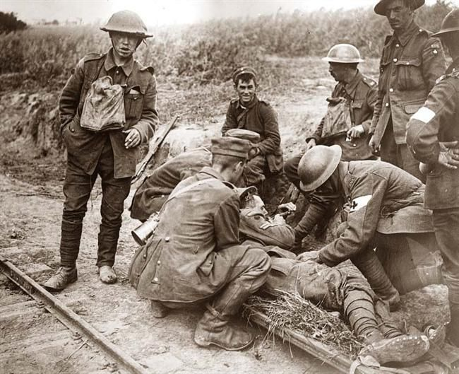 Germans and British soldiers (nobody seems armed )attending to a wounded British soldier of the Great War. WW I