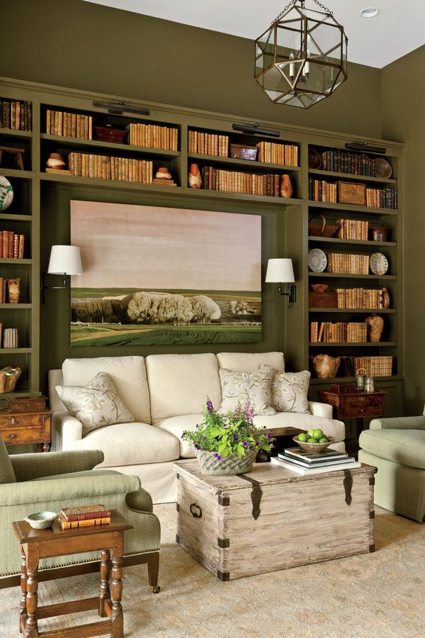 """Just off the living room sits a wonderful, intimate little study that was designed as a purposeful departure from its big, open neighbor. """"It's very important to have that room you can retreat to in the early morning or evening,"""" says Terry. A deep green paint color covers the walls and built-in bookcases, elevating the room's coziness. To counterbalance the depth of the wall color, Phoebe used lighter colors for the curtains, upholstery, and rug. Video: Tour the Study"""