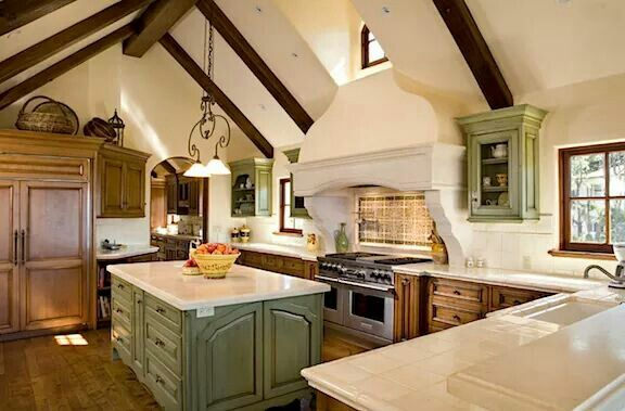 Mediterranean style kitchen. Drawers in complementary soft green island. Integrated fridge. Heavy duty gas range with double ovens. Clean walls. Beams and arched doorway. Love!