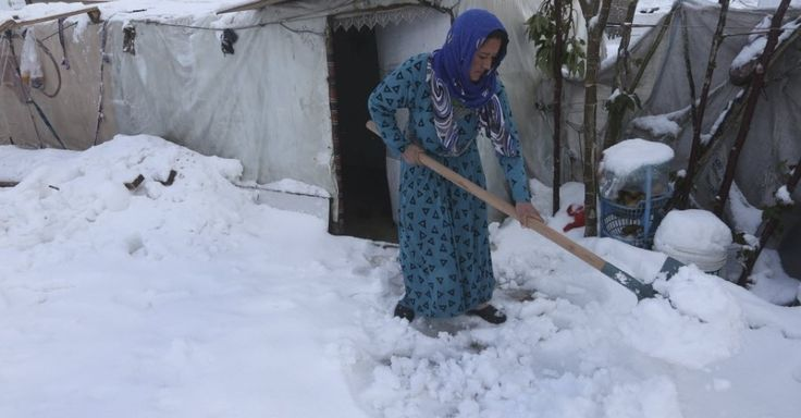 Uma mulher remove a neve em torno de sua barraca em um campo de refugiados na aldeia de al-Majdal, no Líbano.  Fotografia: Hussein Malla/ AP.