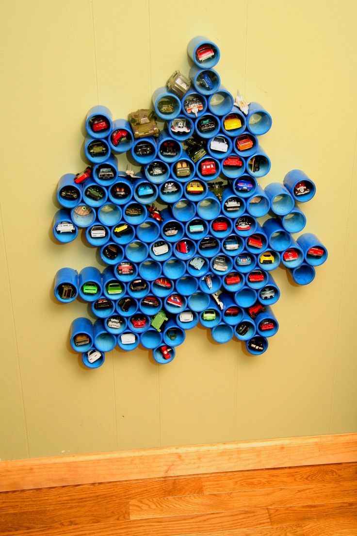 """Cool Hot Wheels or Matchbox car collection holder!  1-1/2"""" diameter pvc pipe dyed blue and glued together with pvc solvent. cut back of pipes at a slight angle so the cars don't roll out.  Glue them together in any random beehive pattern and hang it on the wall at kid height.  They have as much fun putting the cars in and out of the slots as they do playing with the cars."""