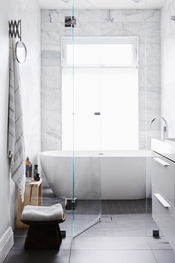 A glass wall divides the wet room from the vanity area. The wet room has a large soaker tub and rain head and is tiled in Carrara marble. The full height window maximizes natural light and allows for a visual link to the outdoors. A neutral palette and clean materials convey a sense of simplicity and calm, perfect for relaxing in the tub.