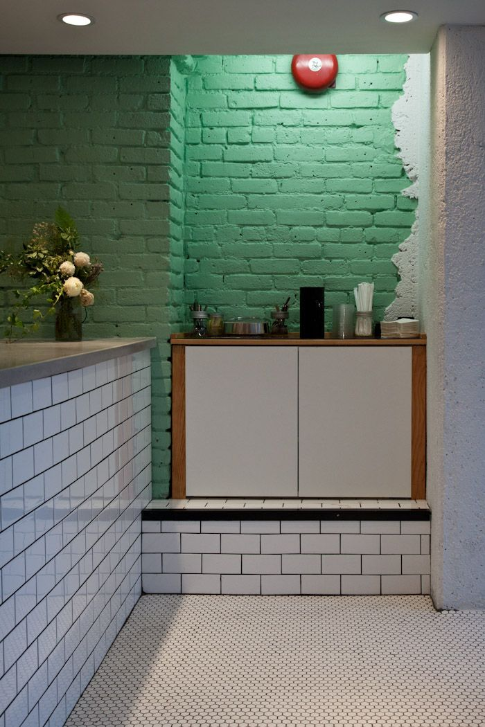 green brick wall + white subway tiles + dark grout