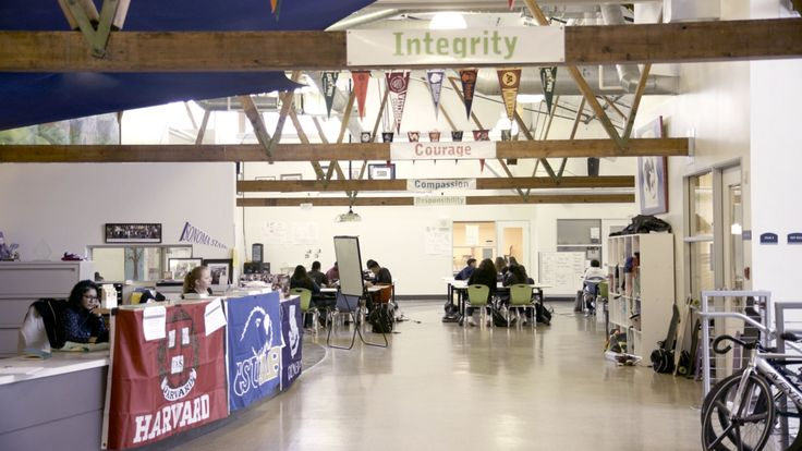 A multipurpose room filled with college banners, students studying at tables, cubbies against one wall, and an open office with two adults sitting behind a desk counter.