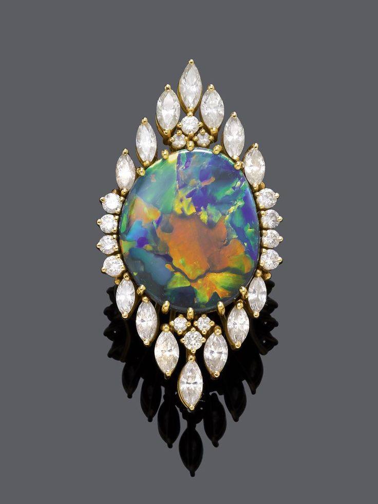 BLACK OPAL AND DIAMOND RING, ca. 1960. Yellow gold 750. Set with 1 very fine black opal, with blue, red, orange, yellow and green colours, of ca. 22,3 x 18,7 x 5,2 mm, surrounded by marquise- and brilliant-cut diamonds, weighing ca. 3.20 ct. Size ca. 51. #opalsaustralia