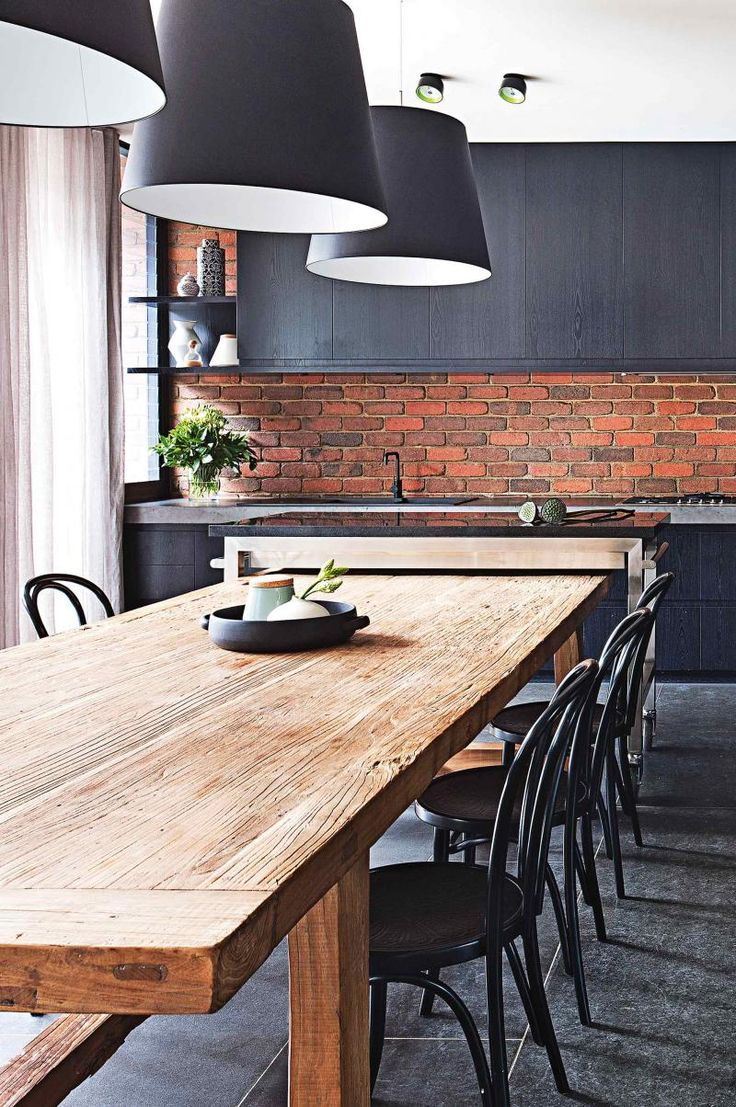 dining space off the kitchen - exposed brick wall, grey cabinetry and raw timber table paired with bentwood chairs