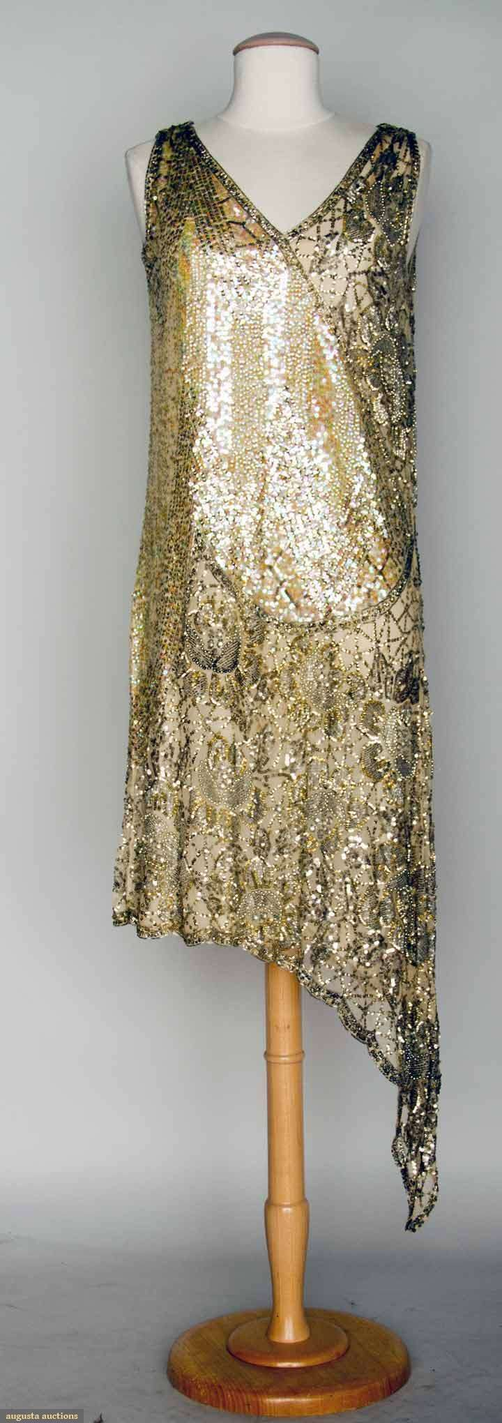 Silver Sequin Party Dress Covered In Opalescent And Metallic Silver Sequins, Rhinestones, Silver Bugle Beads, And Silver Balls, All Worked In Floral And Deco Pattern, Asymmetrical Hem On Left Side    c.1920's   -    Augusta Auctions