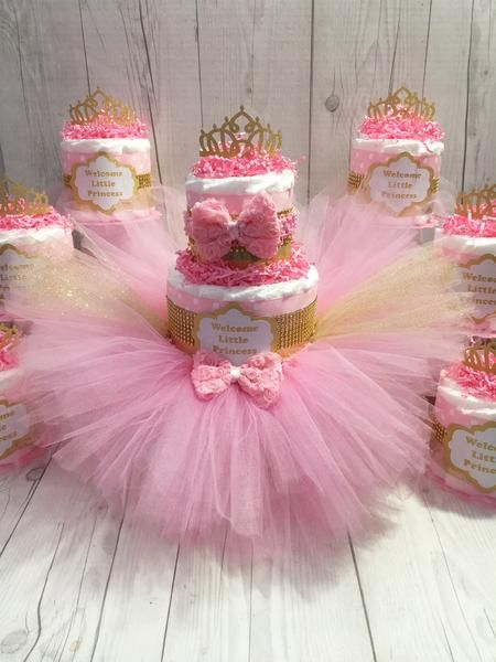 Gorgeous tutu diaper cake will wow all of your guest at your baby shower. Decorated withpink and goldribbon with gold-toned rhinestones, this diaper cake set