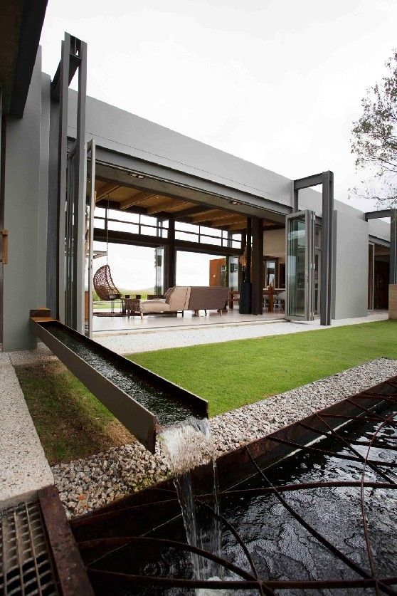 The eco-friendly South African home of architect Gillian Holl uses fresh rainwater to fill a koi pond and swimming pool; excess water can drain through surrounding gravel.