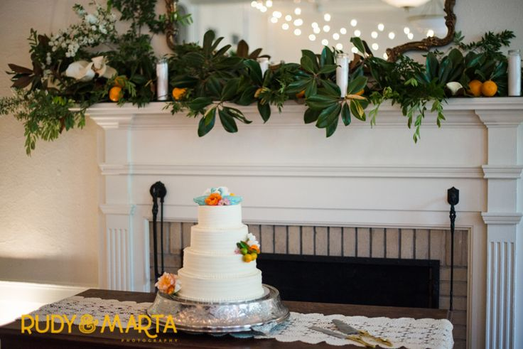 in the historic reception hall, the fireplace mantle is dressed with a lush abundance of magnolia, elm, lemon leaf, fresh citrus and jar candles.  centered on an antique table is an elegant wedding cake simply adorned with white scabiosa, orange ranunculus, peach roses, pink larkspur and a sprig of freshly picked calamondin.