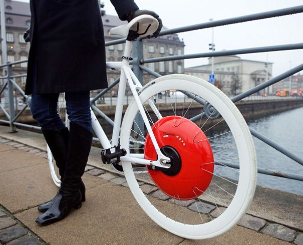 The Copenhagen Wheel | Christine Outram - A striking red wheel-hub that fits the rear wheel of a cycle. It contains a motor, batteries and an internal gear system that allows cyclists to overcome hilly terrains and long distances. The stored pedal power is used up by the hybrid electric motor and is manipulated via a smart phone docked on the handlebars. Cyclists can use data to plan bike routes and see traffic and pollution levels ahead.