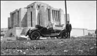 Image No: NB-16-615 Title: The Mormon Temple, Cardston, when it was completed. Date: [ca. 1920-1925] Photographer/Illustrator: Oliver, W.J., Calgary, Alberta Remarks: Entrance facing west. William Oliver beside car.