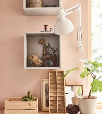 For peaceful home decor, choose what you want to have on display and group it. Use an open cabinet like this square, open, light gray EKET cabinet from IKEA to hold your favorite things in one place as focal points that are easier on the eyes.